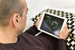 Junger Mann, der einen Film oder eine Reihe in seiner Tablette aufpasst Stockfotos