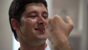 Junger Mann, der einen großen Käfer hält Schabe auf menschlichem Gesicht stock footage