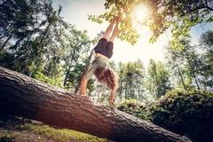 Junger Mann, der einen Handstand auf einem Baumstamm im Wald tut Stockbilder
