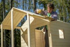 Junger Mann, der einen Holzhammer verwendet, um einen Nagel in ein Dach eines hölzernen p zu regeln Lizenzfreie Stockfotos