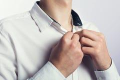 Junger Mann, der einen Knopf knöpft Lizenzfreie Stockfotos