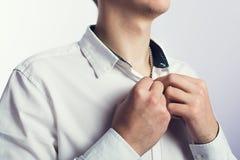 Junger Mann, der einen Knopf knöpft Stockfoto