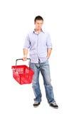 Junger Mann, der einen leeren Einkaufskorb hält Stockfotos