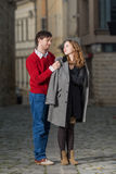 Junger Mann, der einen Mantel auf die Schultern seiner Freundin setzt lizenzfreie stockbilder