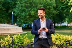 Junger Mann, der in einen Park wartet und sein Telefon hält Stockfotografie