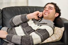 Junger Mann, der einen Telefonaufruf und -c$lächeln bildet Stockfotografie