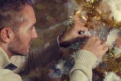 Junger Mann, der einen Weihnachtsbaum verziert Stockbilder