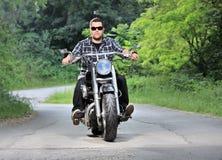 Junger Mann, der einen Zerhacker auf eine Straße reitet Lizenzfreie Stockfotos