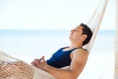 Junger Mann, der in einer Hängematte am Strand schläft Stockfotografie