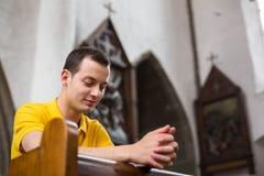 Junger Mann, der in einer Kirche betet Lizenzfreie Stockfotos