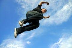 Junger Mann, der in einer Luft springt Stockbild