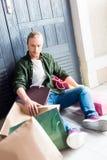 Junger Mann, der Einkaufstaschen beim Stillstehen und Sitzen auf Boden hält Lizenzfreie Stockfotografie