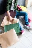 Junger Mann, der Einkaufstaschen beim Stillstehen und Sitzen auf Boden hält Lizenzfreie Stockfotos