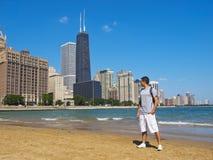 Junger Mann, der entlang der Chicago-Skyline anstarrt Lizenzfreie Stockfotografie