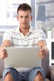 Junger Mann, der entlang des Laptopbildschirms erschrocken anstarrt Stockfotografie
