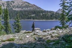 Junger Mann, der entlang eine Spur mit einem Gebirgssee und Berge im Hintergrund geht lizenzfreie stockfotografie