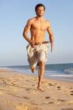 Junger Mann, der entlang Sommer-Strand läuft Stockfoto