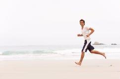 Junger Mann, der entlang Winter-Strand läuft Stockbilder