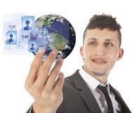 Junger Mann, der Erde mit Social Media-Symbolen lokalisiert auf Weiß hält Lizenzfreies Stockbild