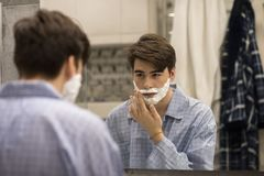 Junger Mann, der für erstes Mal sich rasiert Lizenzfreie Stockfotografie