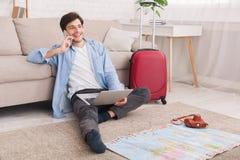 Junger Mann, der für Ferien, beraten mit Mittel sich vorbereitet lizenzfreies stockbild