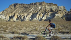 Junger Mann, der Fahrrad auf einen Hintergrund einer Landschaft mit Bergen fährt Stockbilder