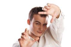 Junger Mann, der Feld mit dem Finger auf Weiß bildet stockfoto