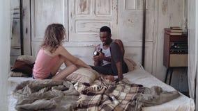 Junger Mann, der Foto der Frau in den Pyjamas auf der Bewegenfilmkamera macht Gemischtrassige Paare, die auf dem Bett am Morgen s Stockbild