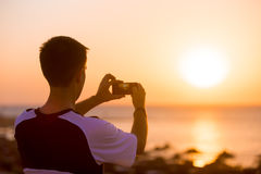 Junger Mann, der Foto des Seesonnenuntergangs macht Lizenzfreies Stockfoto