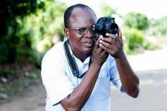 Junger Mann, der Fotos mit einer Digitalkamera in der Kampagne macht Stockbilder