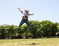 Junger Mann, der frei in den Park glaubt Stockfotos