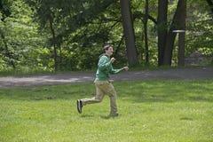 Junger Mann, der Frisbee am Park spielt Stockbilder