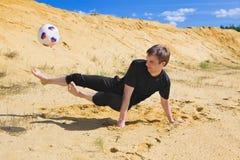 Junger Mann, der Fußball auf Strand spielt Stockfoto