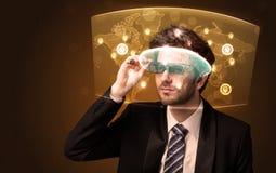 Junger Mann, der futuristische Karte des Sozialen Netzes betrachtet Stockbilder