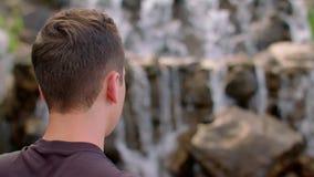 Junger Mann, der Gebirgswasserfall betrachtet Wanderer, der nahe Gebirgswasserfall stillsteht stock video