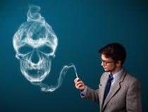 Junger Mann, der gefährliche Zigarette mit giftigem Schädelrauche raucht Lizenzfreies Stockfoto