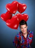 Junger Mann, der geformte Ballone des Herzens hält Stockbild