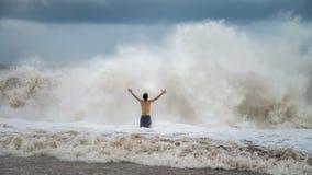 Junger Mann, der gegen die Meereswellen mit Spritzen in einem bewölkten Sturmwetter steht Stockfotos