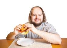 Junger Mann, der geht, Burger zu essen Getrennt auf weißem Hintergrund Lizenzfreie Stockbilder