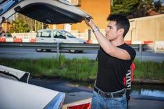 Junger Mann, der Gepäck und Tasche aus Autokofferraum heraus nimmt Stockbild