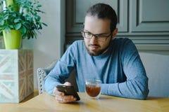 Junger Mann, der Geschäft im Café mit Kaffee tätigt Lizenzfreie Stockfotos