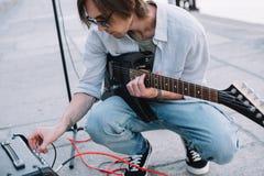 Junger Mann, der Gitarrenverstärker bei der Ausführung justiert lizenzfreie stockbilder