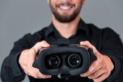 Junger Mann, der Gläser eines VR-Kopfhörers verwendet Stockbild
