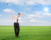 Junger Mann, der Golf auf einem Feld spielt Stockfotografie