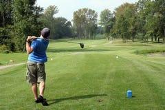 Junger Mann, der Golf spielt Stockfoto