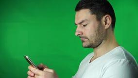 Junger Mann, der grünen Schirmhintergrund des Smartphone verwendet stock video