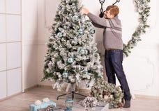 Junger Mann, der grünen Weihnachtsbaum mit Lichtern und Bällen verziert Stockbild