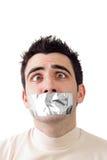 Junger Mann, der graues Kanalband auf seinem Mund hat Stockfotografie