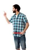 Junger Mann, der großen roten Bleistift hält Stockfotografie
