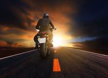 Junger Mann, der großes Motorrad auf Asphaltlandstraßengebrauch für peopl reitet lizenzfreie stockbilder